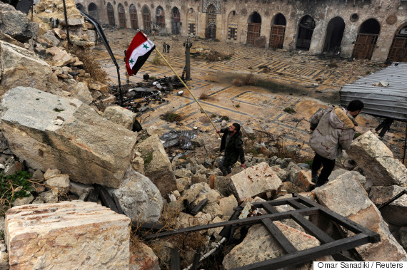 A member of forces loyal to Syria's President Bashar al-Assad attempts to erect the Syrian national flag inside the Umayyad mosque, in the government-controlled area of Aleppo, during a media tour, Syria December 13, 2016. REUTERS/Omar Sanadiki     TPX IMAGES OF THE DAY